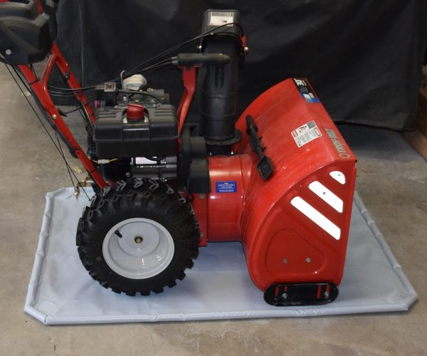 Red snowblower on grey antiskid mat